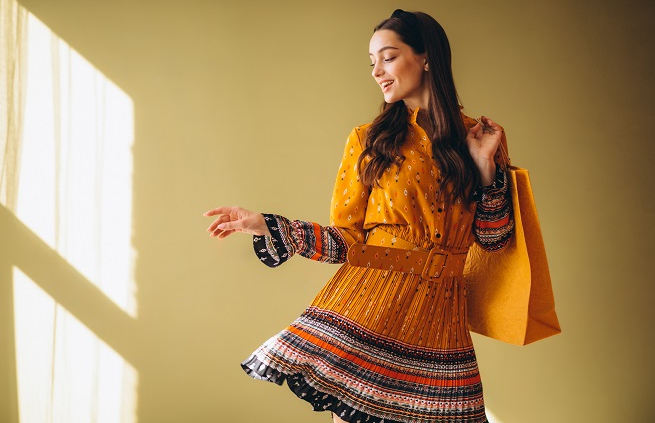 Fashion Trends - smiling girl with yellow dress and a big orange bag