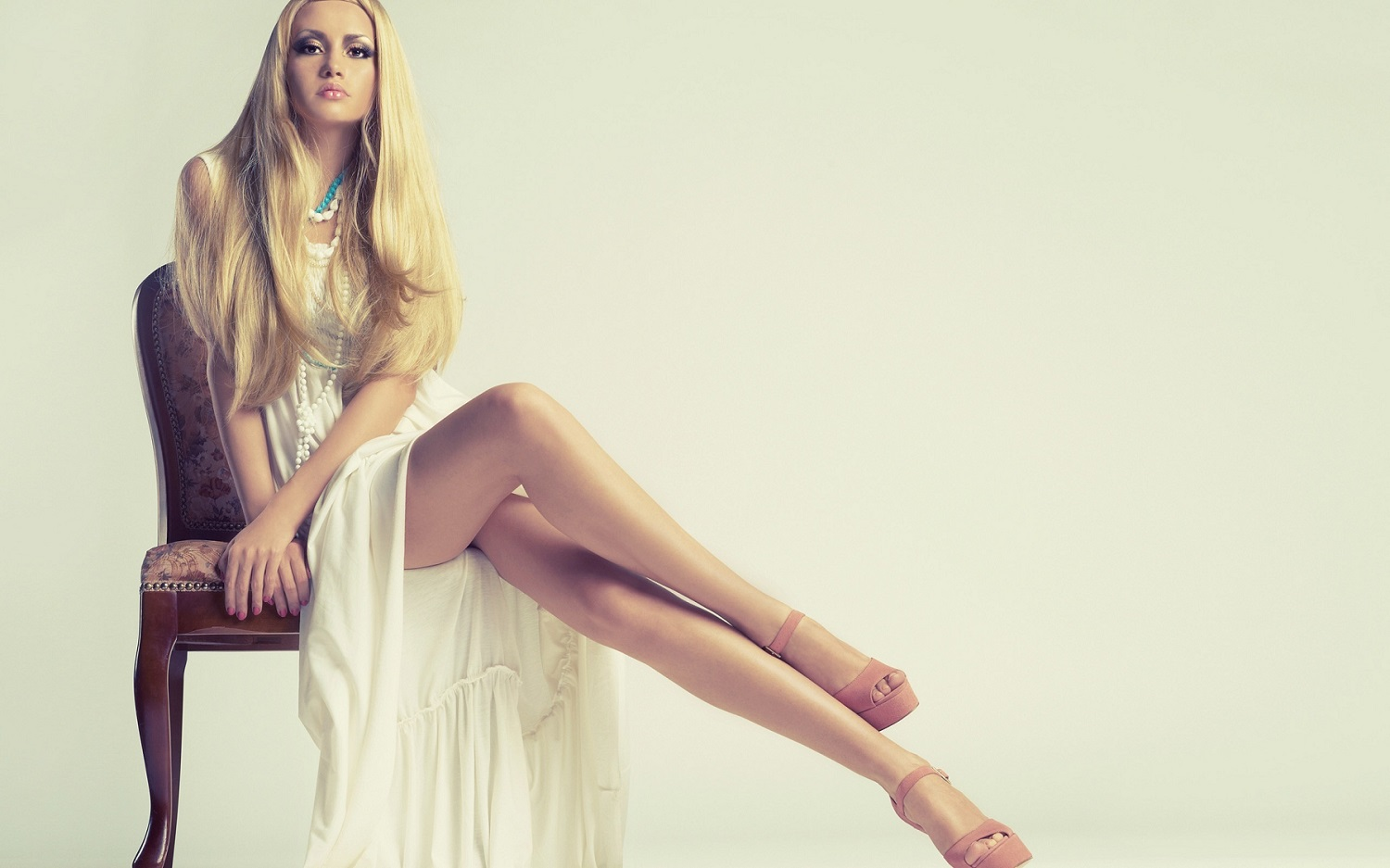 Fashion Trends - Girl with long blond hair in white dress sitting on vintage chair